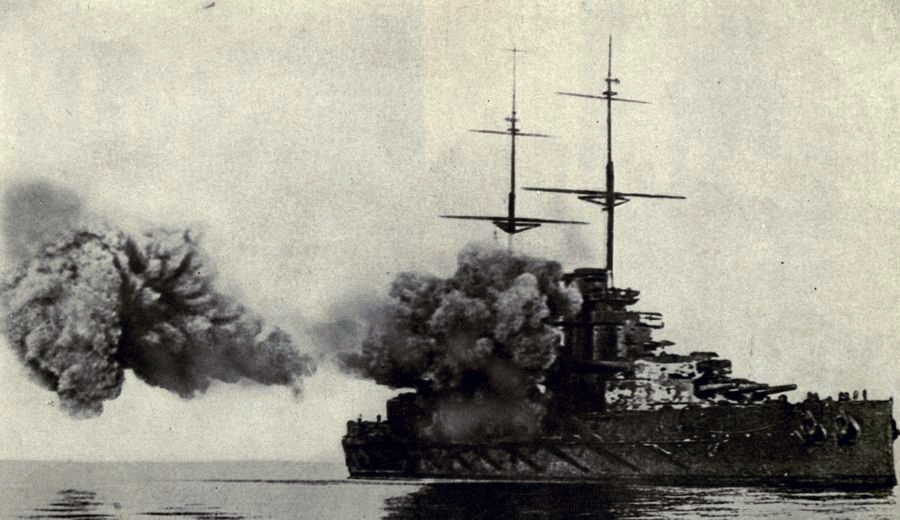 An unidentified British battleship fires its main armament.