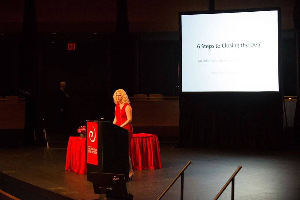 """Jane speaking on stage at the Institute for Integrative Nutrition annual Conference at Lincoln Center, NYC. """"6 Steps to Closing the Deal: A Heart-centered Approach to Sales"""""""