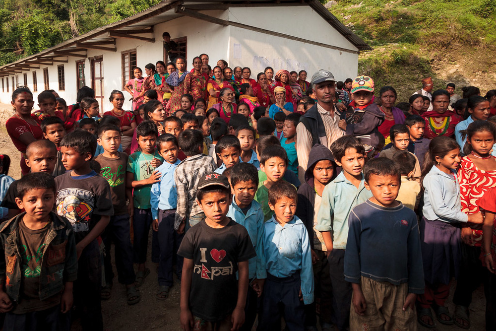 The school children gather outside the hut before being called in to receive their bags.