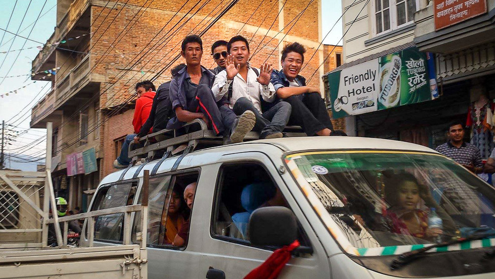 With the severe shortage of fuel in Nepal, local buses carry as many people as possible including using the luggage racks on top to carry passengers.