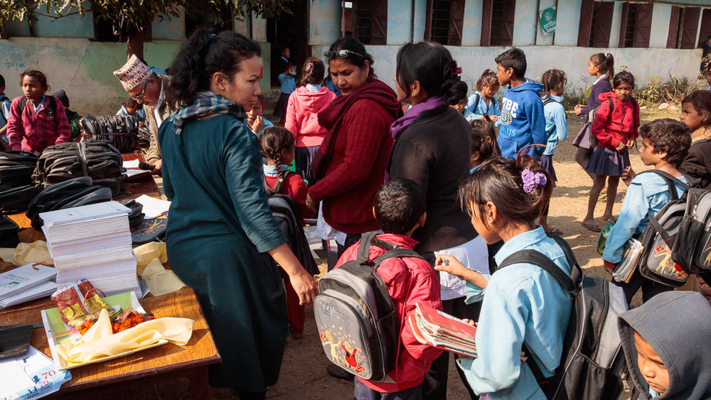 Rewati Gurung handing out school bags to the children in Dudhauli, Sindhuli.
