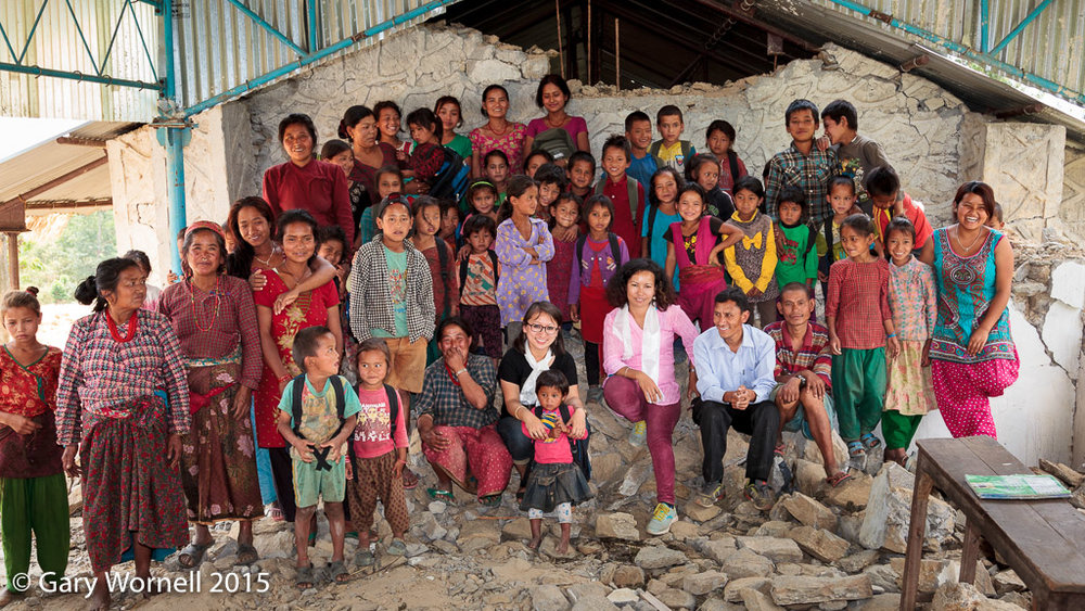 Group photo in the rubble of the collapsed school with the surviving children from the village, teachers, principal, parents and Rewati Gurung - founder of Moving Mountain School Bag and Menka Batachan volunteering.
