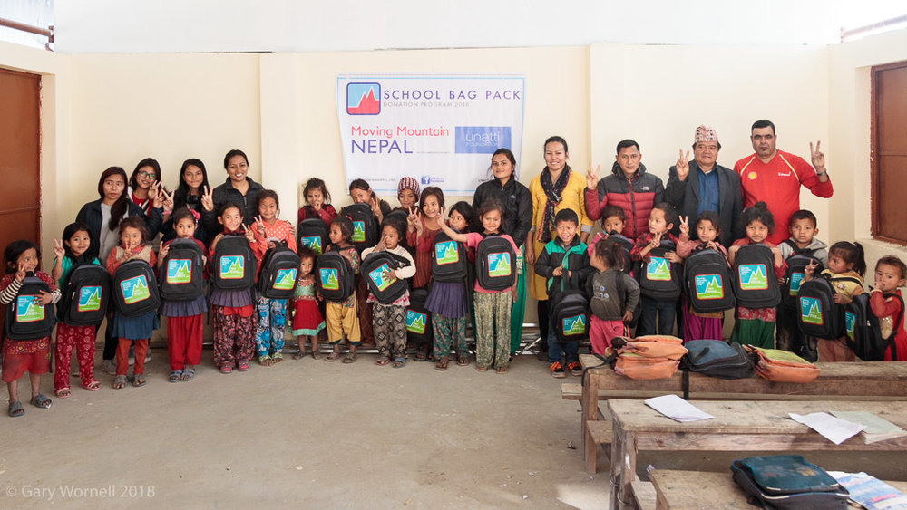 Group shot inside the new school, 30 months after the earthquakes in 2015 with teachers, community members, Rewati Gurung and volunteers from Unatti foundation who supported during the packing and donation day.