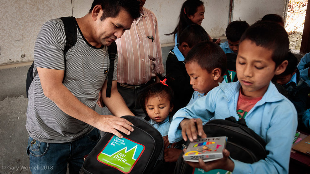 Ganisham Gurung helps a young student go through the contents of her new school bag.