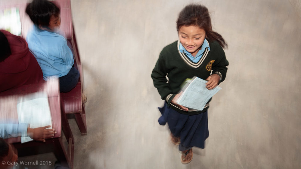 A young girl runs to her desk in preparation for the school bag donation ceremony.