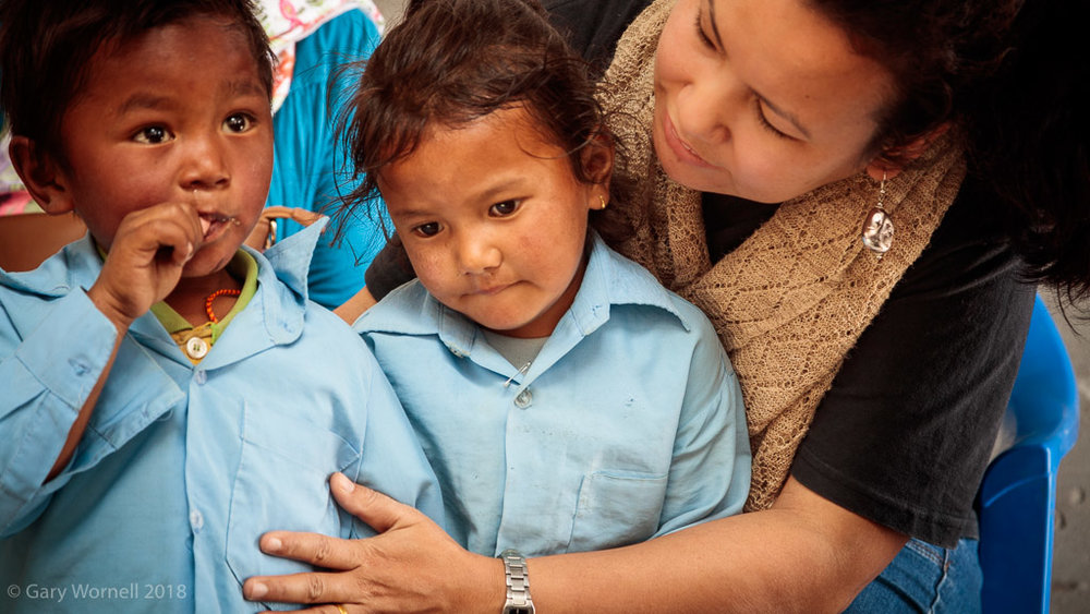 Rewati Gurung hugs two Primary school children during the donation at Shree Tarevire Primary School.
