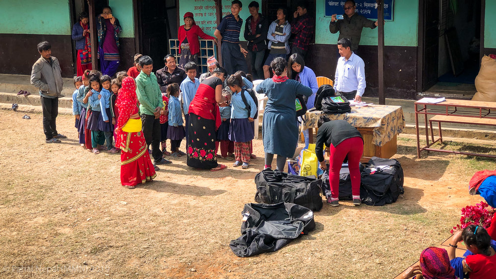 Children line up to receive their school bags with the help of donations and volunteers from Unatti Foundation in Bhaktapur.