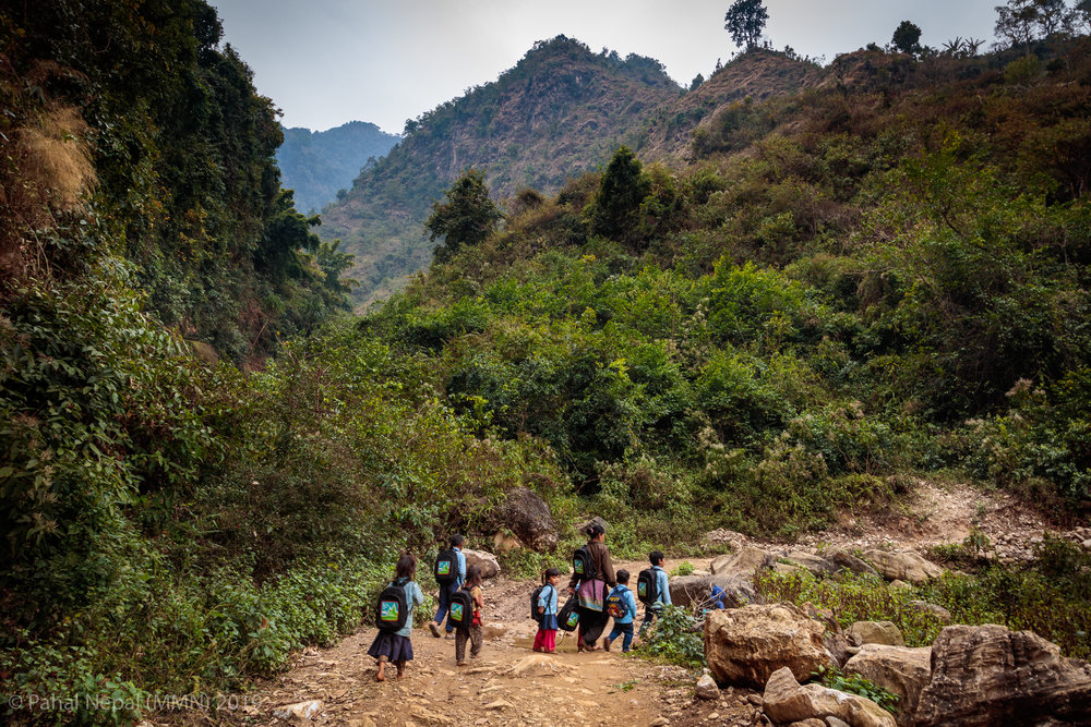 School children from Bhumistan basic school - Dadhing walking home with a mother through the jungle after Moving Mountain Nepal NGO's Valentine's Day donation program.