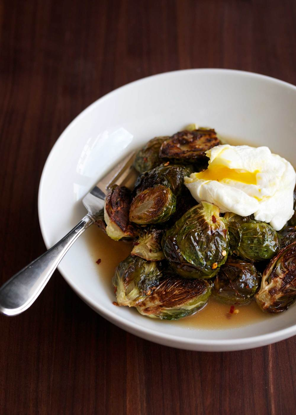 crispy brussels sprouts with bacon dashi broth and poached egg on top
