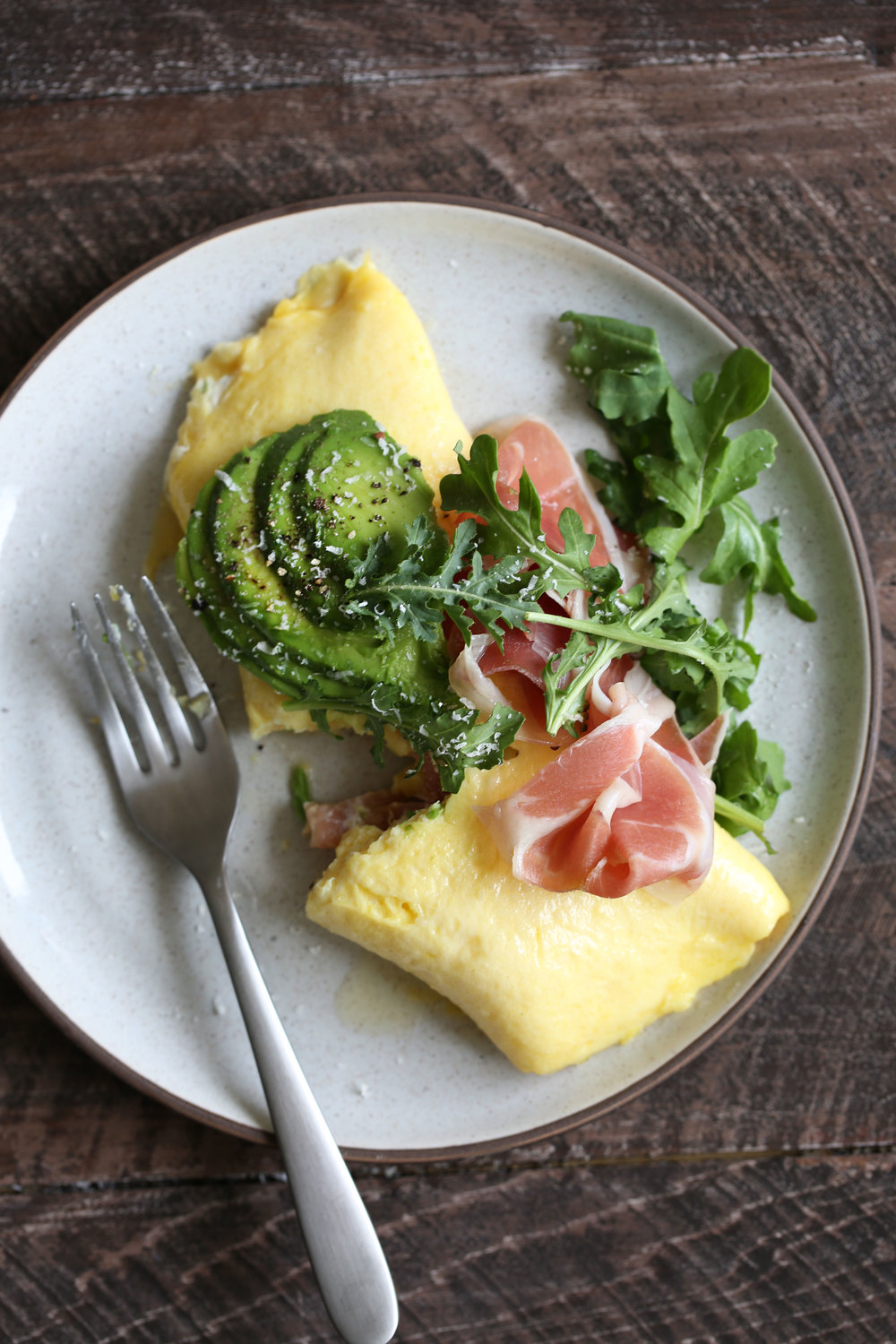 French Omelette with Prosciutto, Cheese Avocado & Arugula eaten