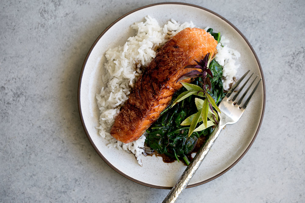 crispy salmon with soy tamarind sauce over sautéed spinach