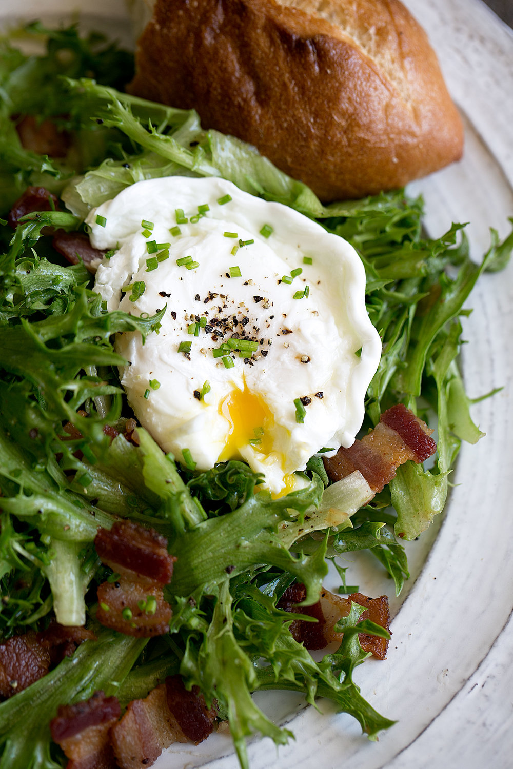bacon and frisée salad with a poached egg closeup