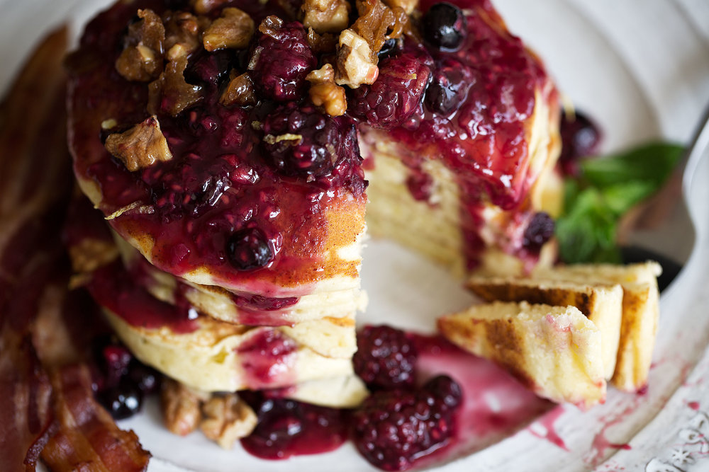 lemon ricotta pancakes with mixed berry compote and candied walnuts bite