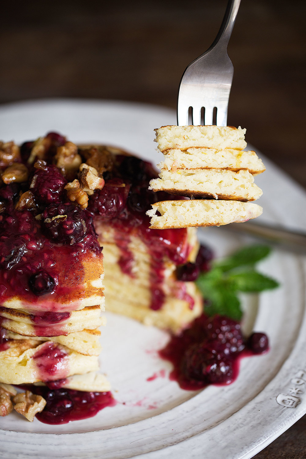 lemon ricotta pancakes with mixed berry compote and candied walnuts bite with fork