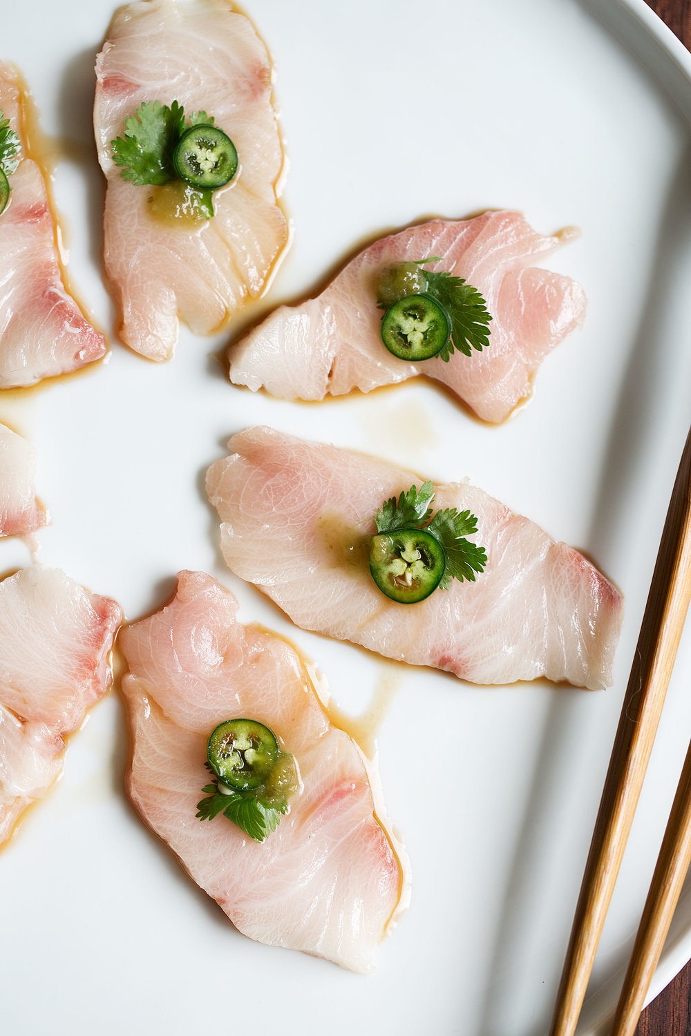 yellowtail sashimi with serrano and ponzu closeup