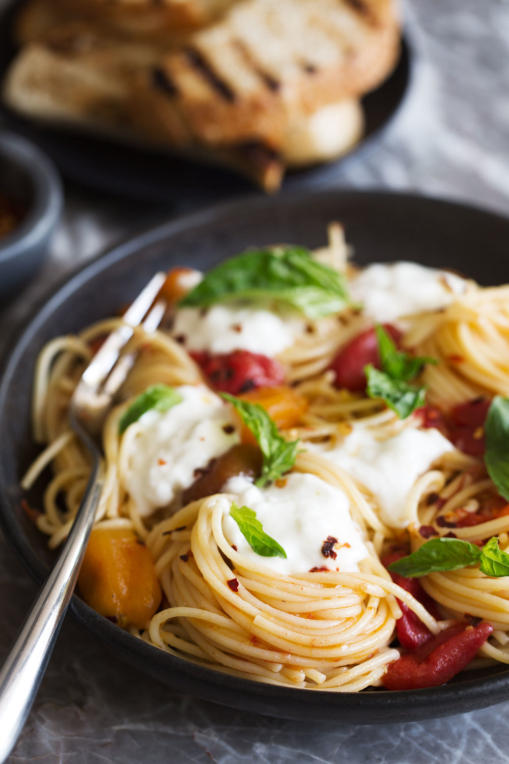 side view spaghetti with burrata and confit tomato