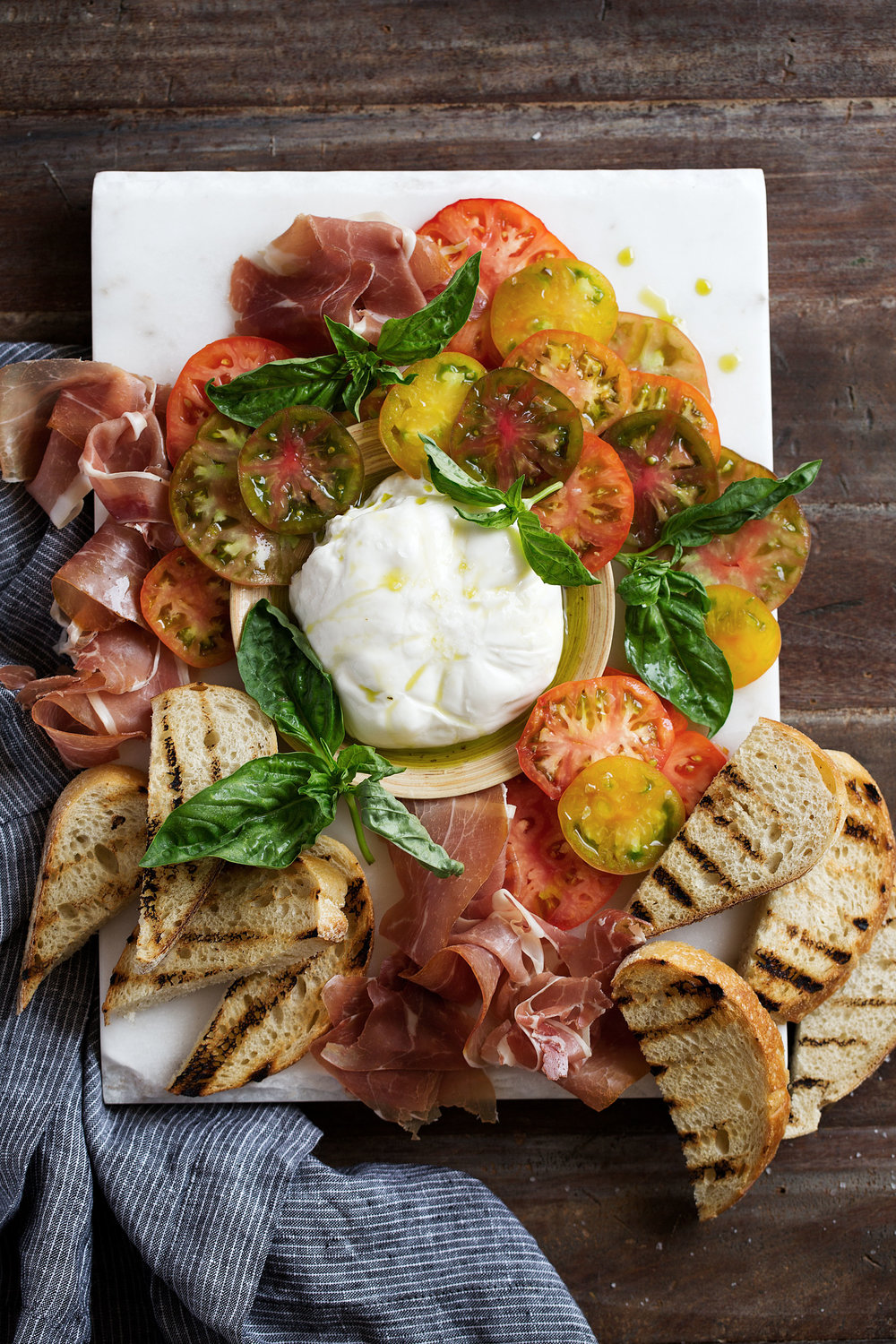 heirloom tomato, prosciutto, and burrata with garlic-basil oil and grilled bread