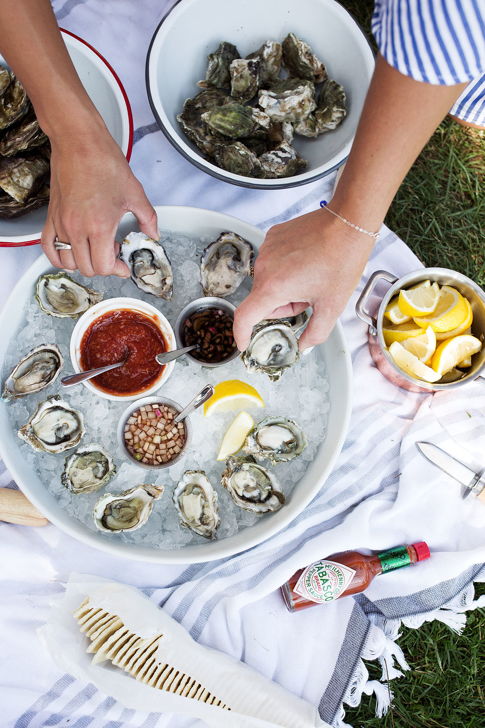 reaching for oysters from platter