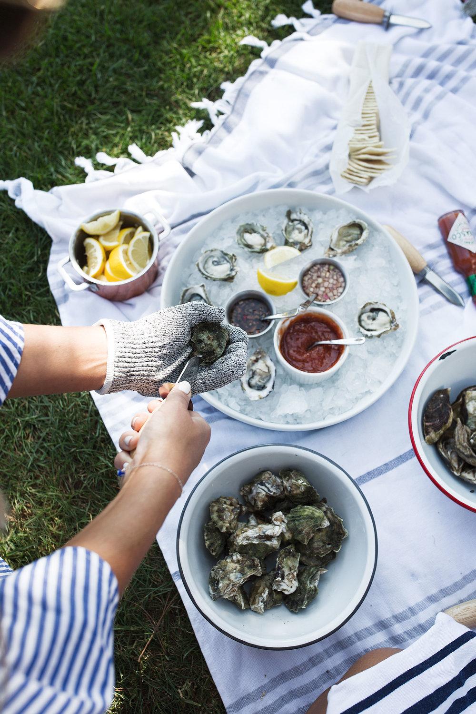 hands shucking an oyster