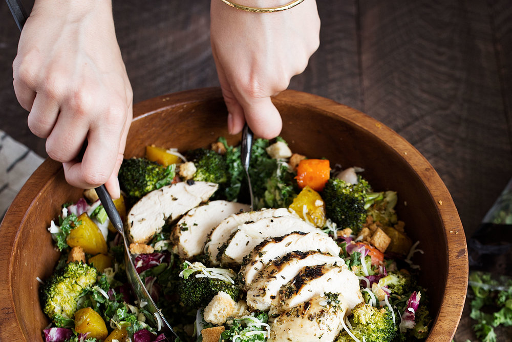 closeup kale salad with roasted vegetables and herb roasted chicken