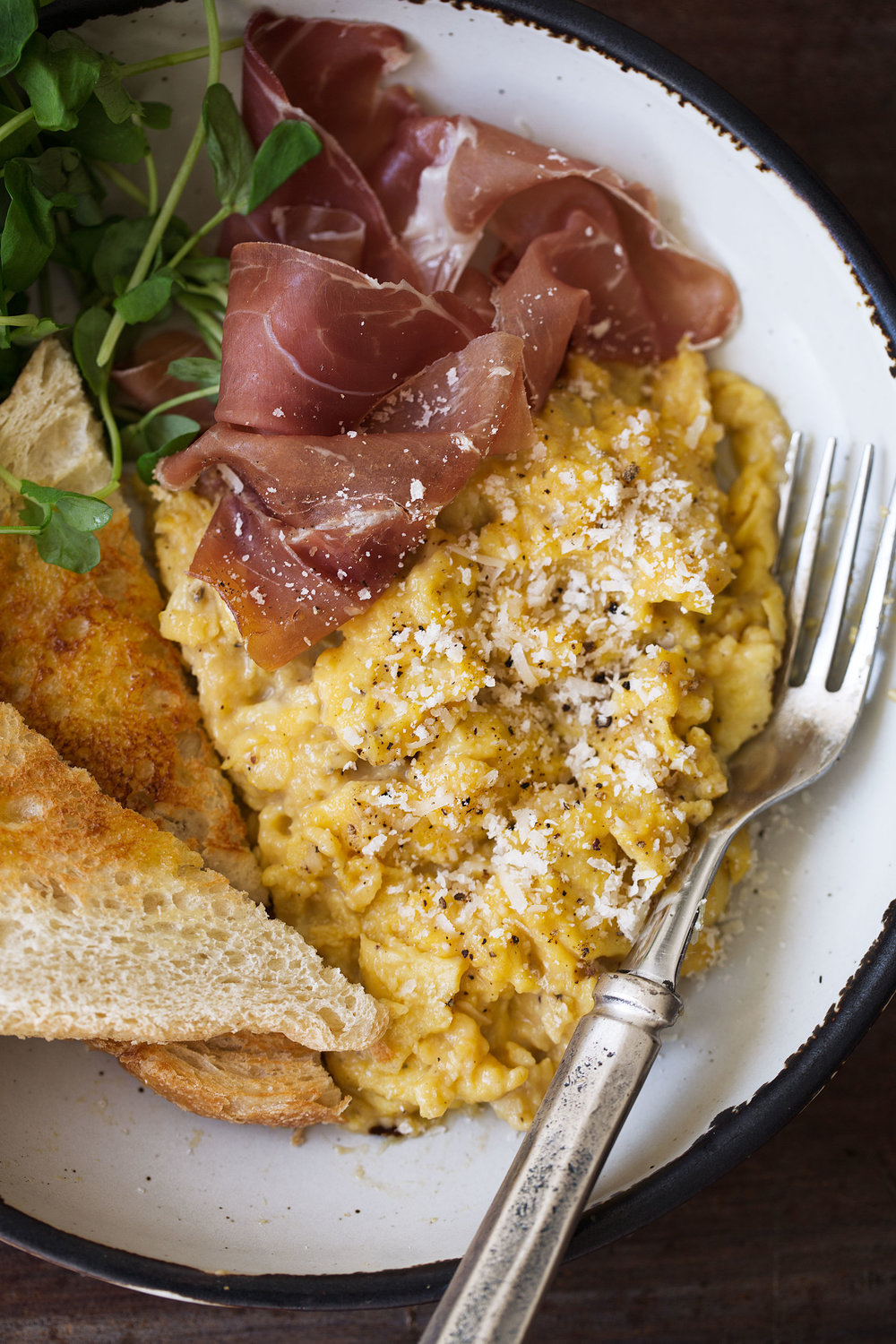 cacio e pepe slow scrambled eggs with prosciutto recipe from cooking with cocktail rings closeup