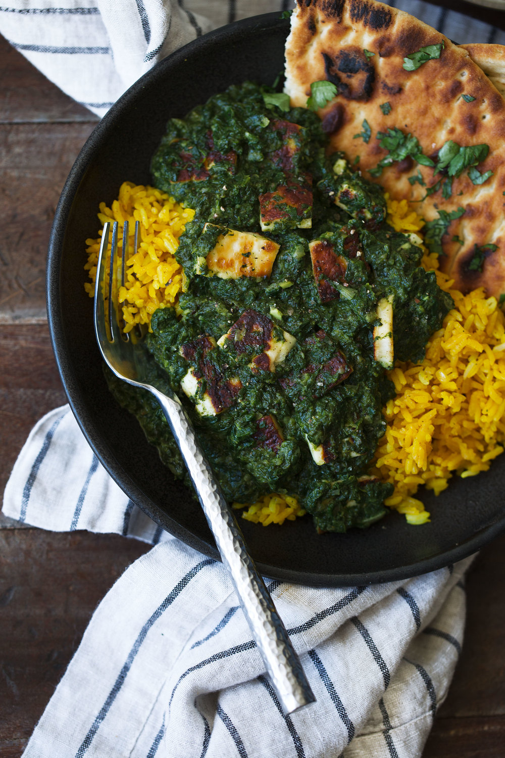 closeup saag paneer over tumeric rice with naan cooking with cocktail rings