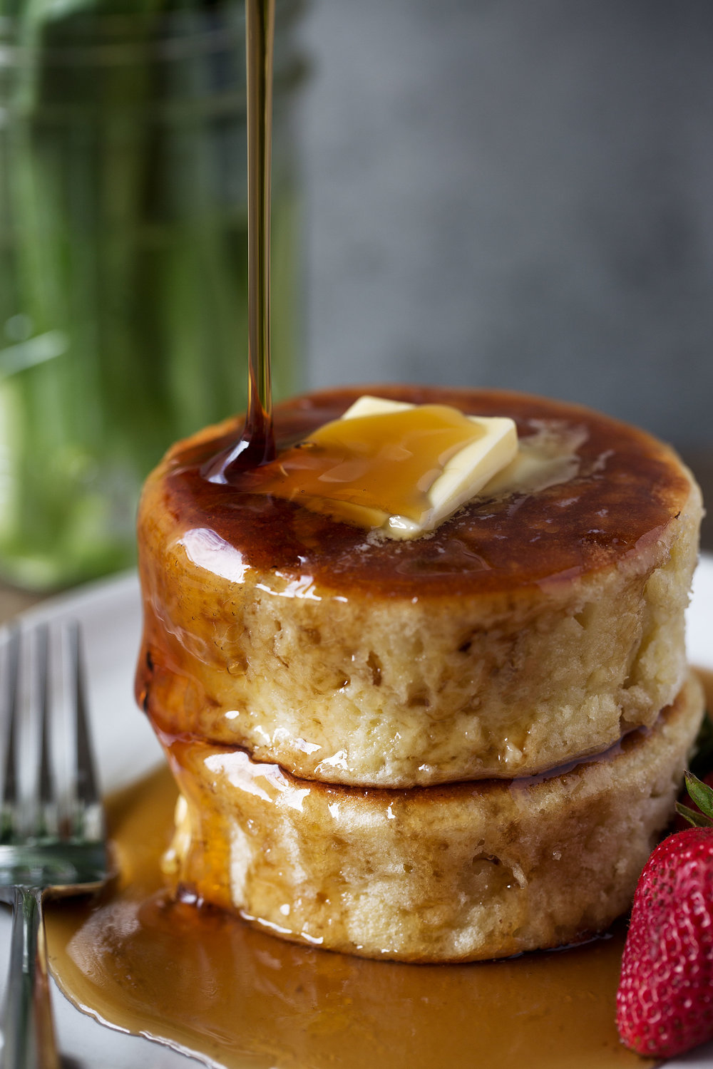 Japanese-style Soufflé Pancakes covered in syrup cooking with cocktail rings