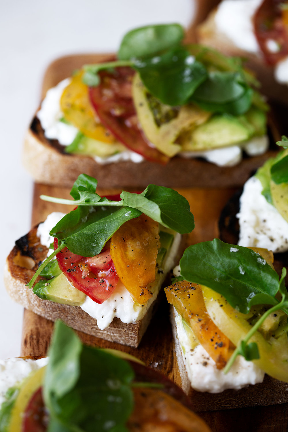 Heirloom Tomato, Avocado & Burrata Tartines recipe from cooking with cocktail rings closeup