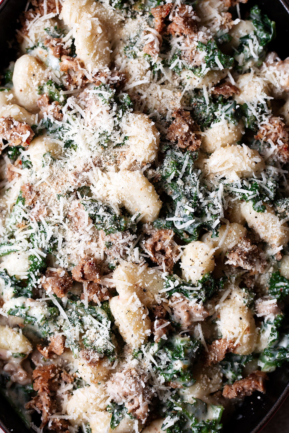sausage and kale gnocchi with garlic cream sauce cooking with cocktail rings