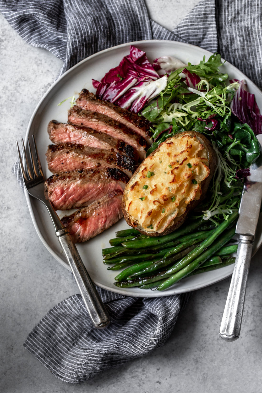 Cheesy Cheddar Twice Baked Potatoes recipe with seared steak from cooking with cocktail rings