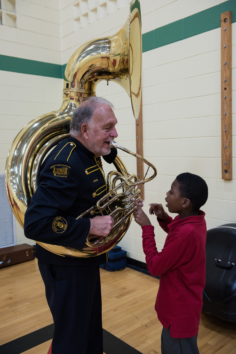 Band Member Jim Hopper showing a student his sousaphone.