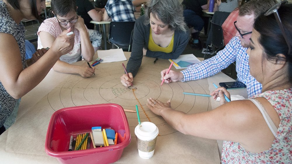 "A group works together on a mandala as part of a ""Deep Dive"" session."