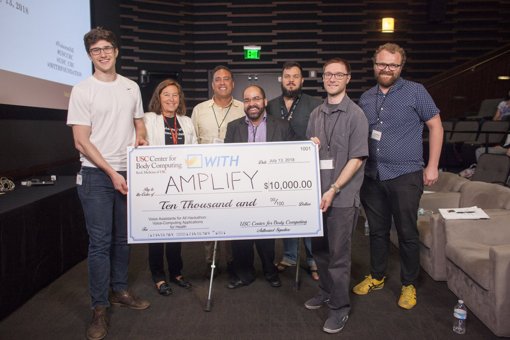 Executive Director of the USC Center for Body Computing Dr. Leslie Saxon, and other Hackathon judges, present the $10,000 check to the winners, Team Amplify.