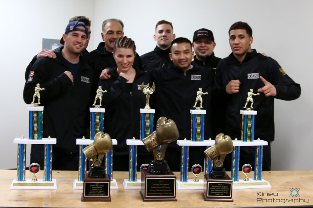 Portland Boxing Club teammates at the 2017 Northern New England Golden Gloves Championships in Essex Jct, VT. (Back row, left to right) Ivan Papkee (partially blocked), Head Coach Bobby Russo, Zach DiSilva, and Coach Jack Lumus. (Front row, left to right) Jason Quirk, Kate Zehr, Danny Pang and Josniel Castro. Photo courtesy of Kineo Photography.