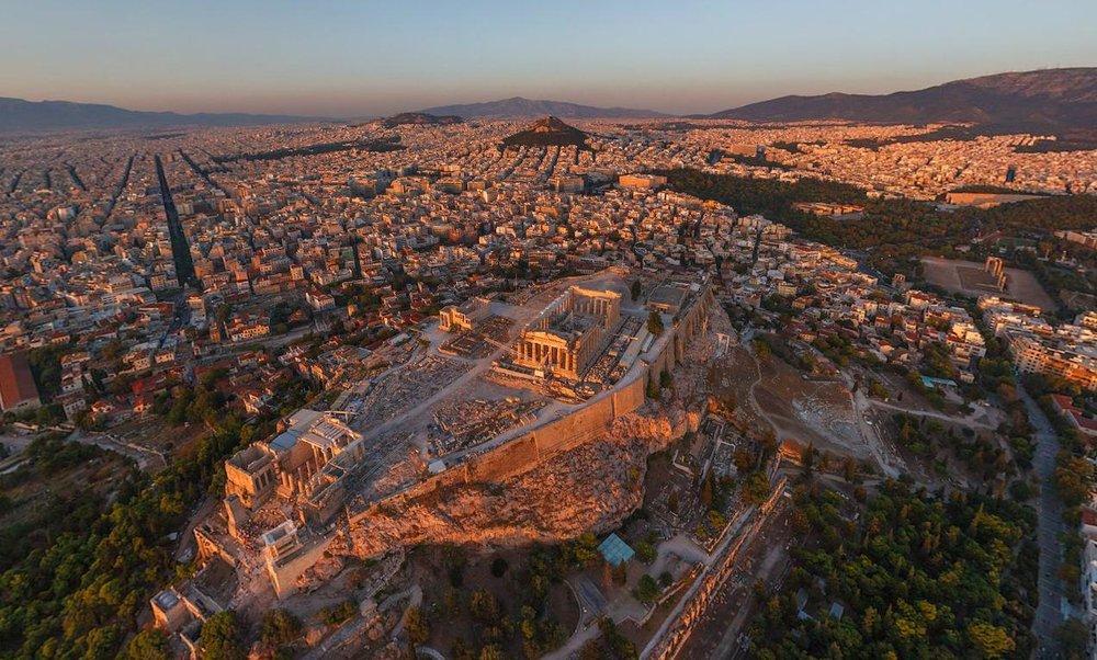 Остатки древнего города на фоне современных Афин