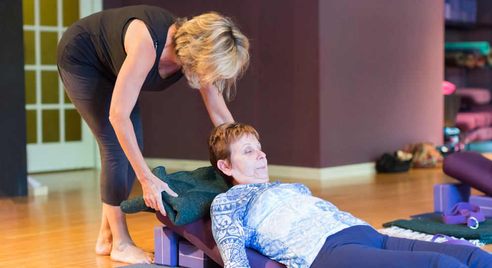 Marianne is helping a student settle into a restorative pose during the class.