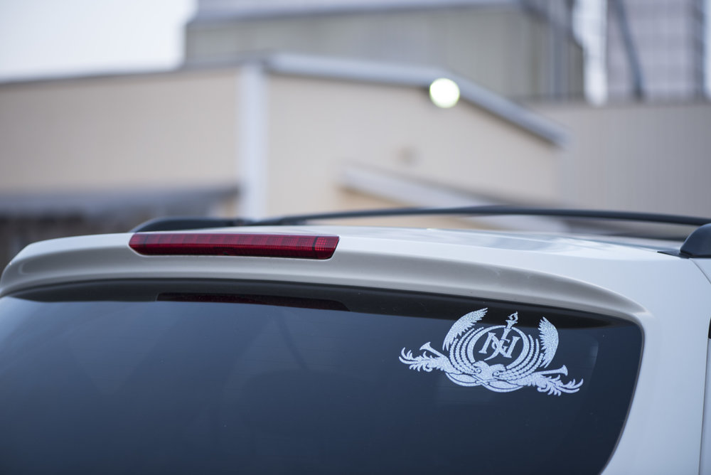 The initials of Naasón Joaquín García, the International Director of the Light of the World church and the claimed Living Apostle of God, appear in the form of a car decal on the vehicle of a church member.
