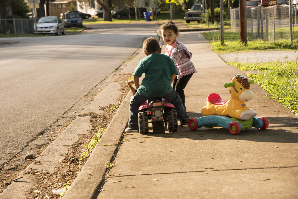 Georgia Burkins' grandchildren play on the sidewalk near her house, which sits on West 13th Avenue, just around the corner from the Light of the World church.