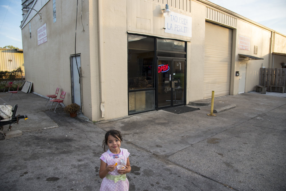 Aurora Guillen, 5, stands outside of La Perlita, the taquería where her mother, Irma Guillen, volunteers her time. La Perlita is owned by the Light of the World church whose sanctuary stands across the street.
