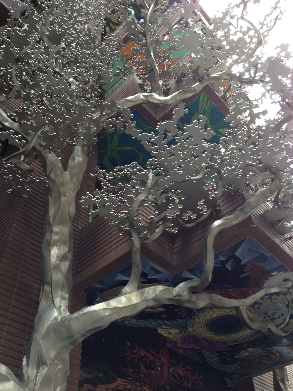 A metal tree next to the artists' building entrance.