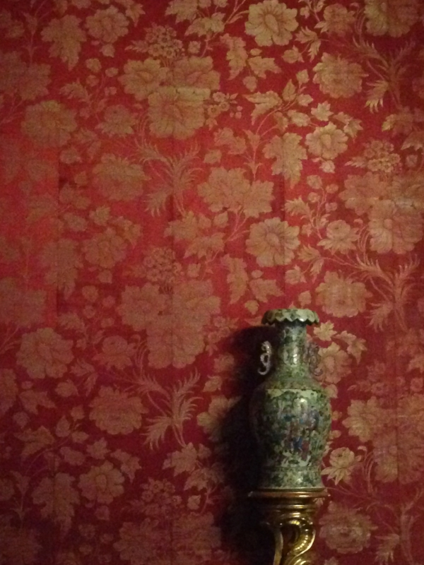 Ornate wallpaper and a vase in the Palazzo Pitti.