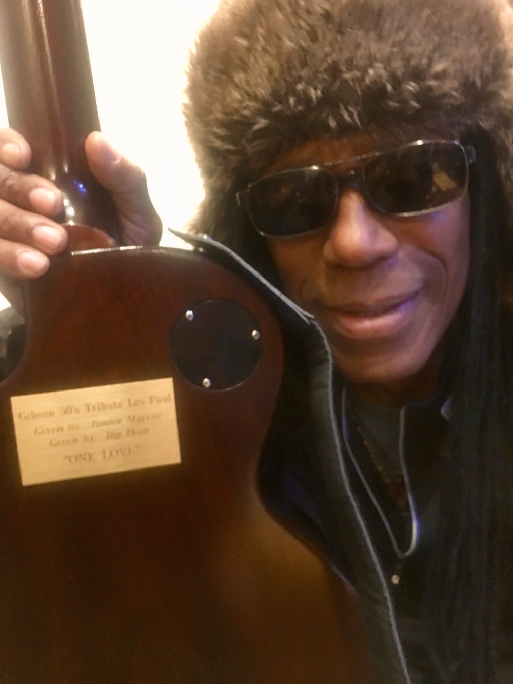 Julian Junior Marvin with the engraved message on the back of his gifted guitar from Dean Rubenstein.