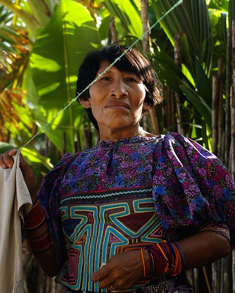 A Guna woman wearing a mola stands next to her clothes-line in Kuna Yala, Panama.