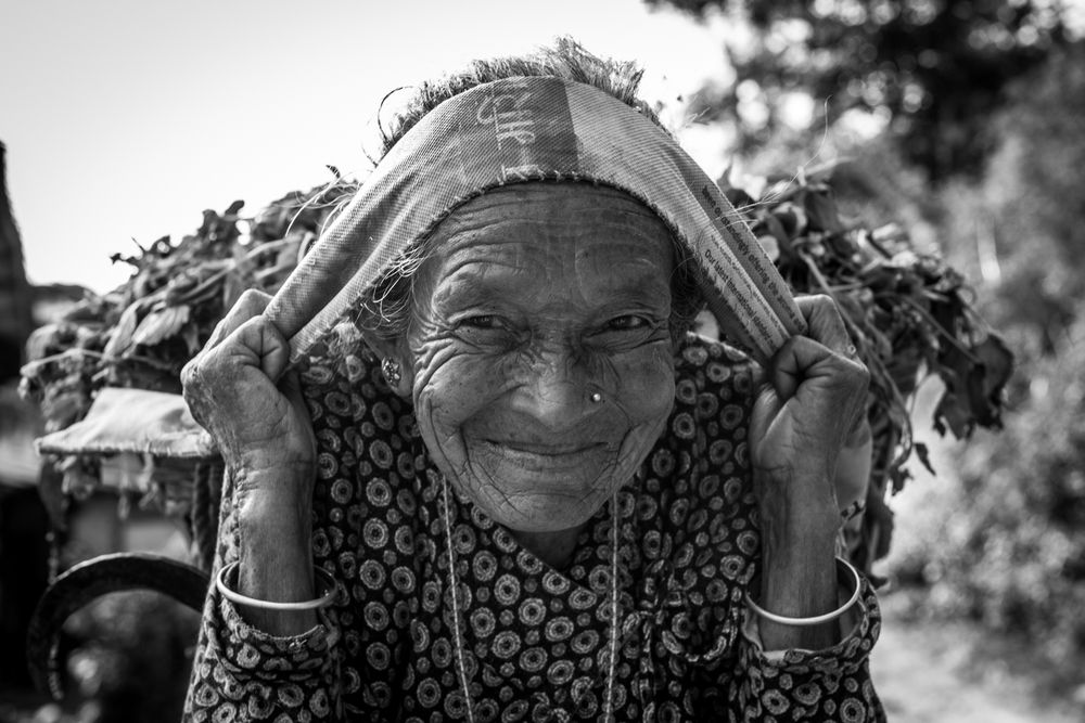 An elder woman flashes a smile as she walks passed - Gouldhunga, Nepal.