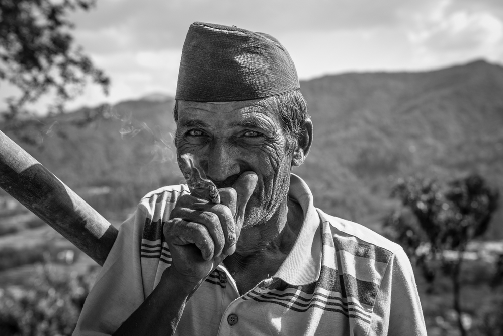 After losing his house in the recent earthquakes in Nepal, he joins our team of relief workers to help build his temporary bamboo shelter. After some hard work he takes a much needed smoke break - Ramkot, Nepal.
