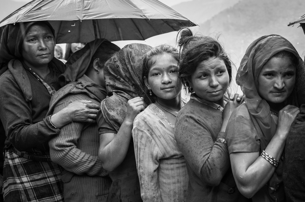 Women patiently wait in line, eager to collect food supplies weeks after the earthquake happened on April 25th, 2015 - Khiping, Nepal.