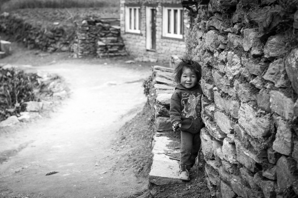 A boy plays hide and seek outside of his home - Lukla, Nepal.