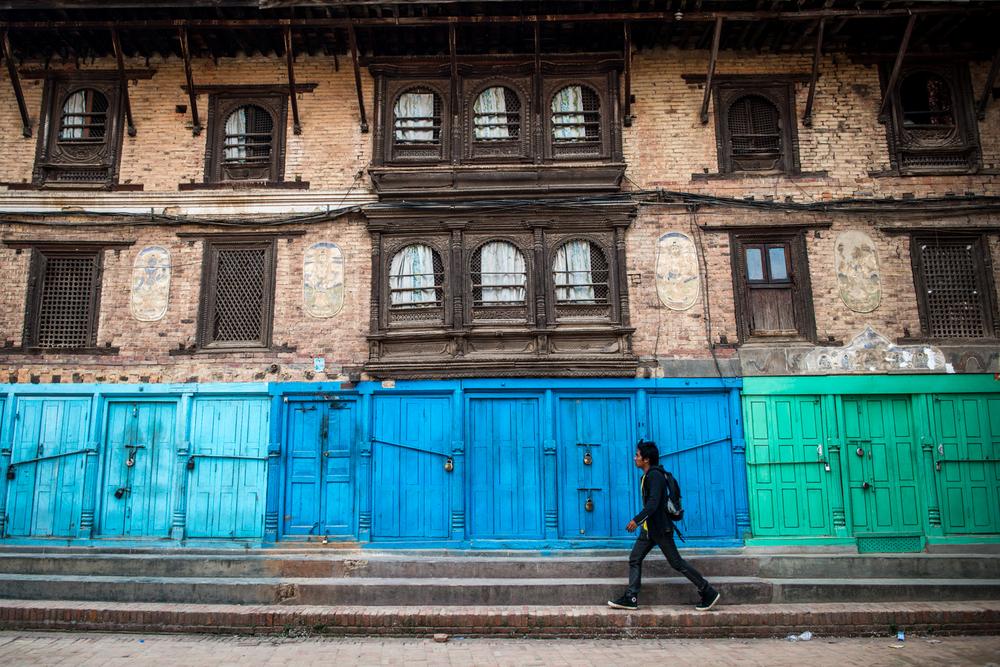 A man walks along closed shops near Durbar Square - Kathmandu, Nepal.