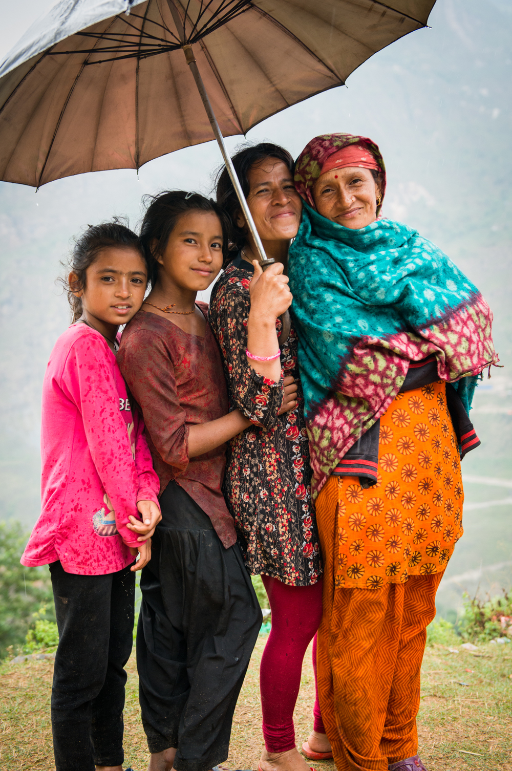 A grandmother, mother and her two daughters seek shelter in the rain - Khiping, Nepal.