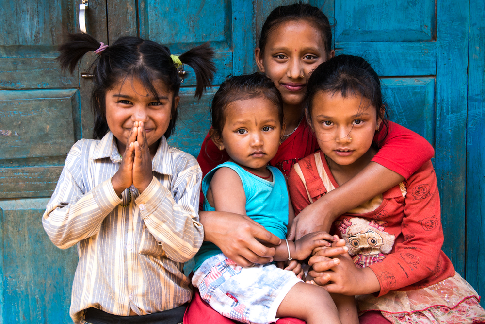 A girl greets with a Namaste as her felow siblings look on curiously - Khari, Nepal.